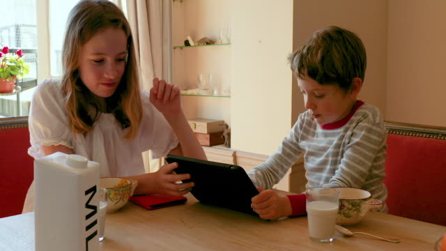 a young boy having breakfast with his digital tablet, morning - carton stock videos & royalty-free footage