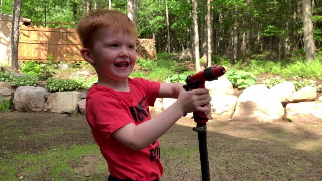 young boy having fun spraying hose in summer - squirt video stock e b–roll