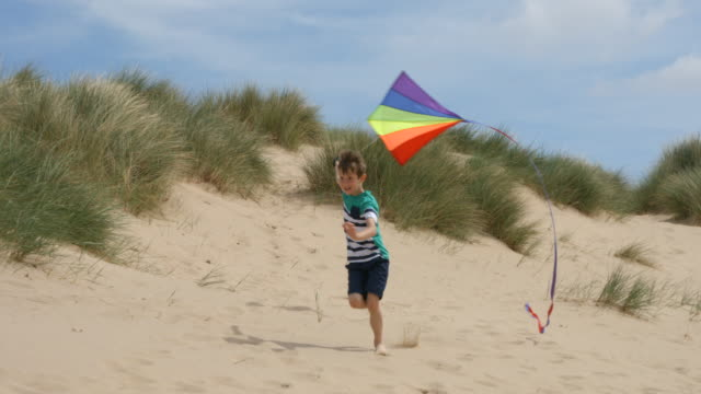 a young boy having great fun running along the beachside sand dunes flying his kite. - shorts stock videos & royalty-free footage