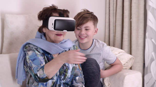 young boy helps his 90 years old great grandmother using a high end virtual reality head set