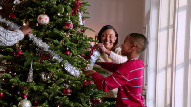young boy helps mom and dad string tinsel on christmas tree - christmas decoration stock videos & royalty-free footage
