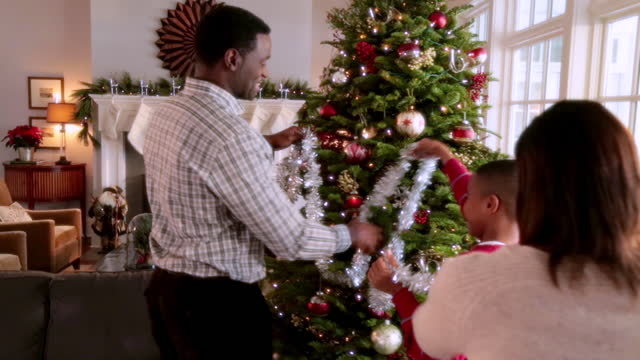 vídeos de stock, filmes e b-roll de young boy helps mom and dad string tinsel on christmas tree - decoração de natal