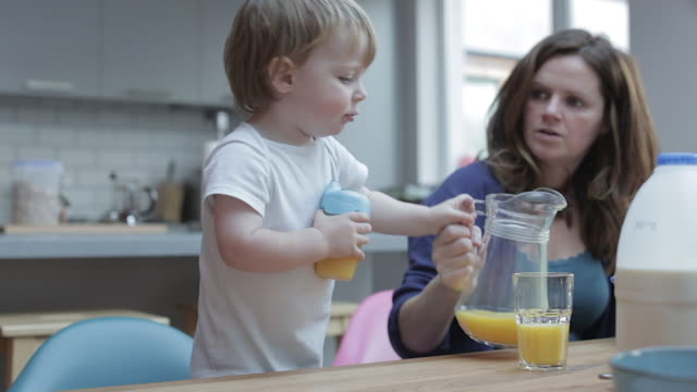 young boy helps pour a glass of orange juice - saft stock-videos und b-roll-filmmaterial