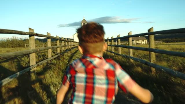 vídeos de stock, filmes e b-roll de jovem rapaz caminhadas ao longo do caminho em direção a igreja rural - igreja