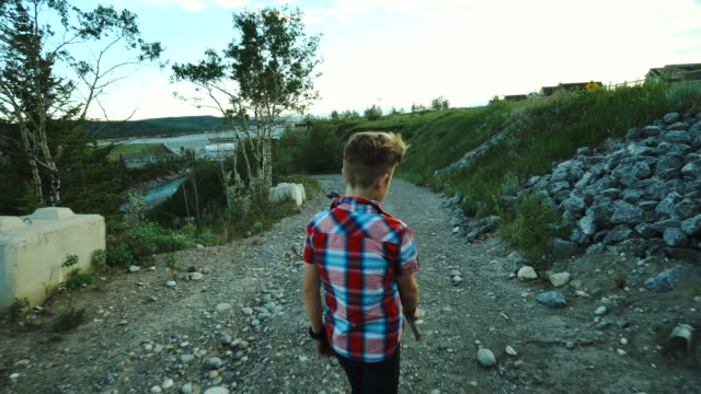 young boy hikes along rural path towards dam, walking stick - walking point of view stock videos and b-roll footage