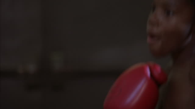 young boy hitting punch bag at boxing club, illinois, chicago available in hd. - boxing glove stock videos & royalty-free footage