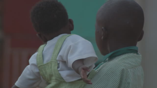 stockvideo's en b-roll-footage met ms young boy holding baby / buikwe, uganda - carrying