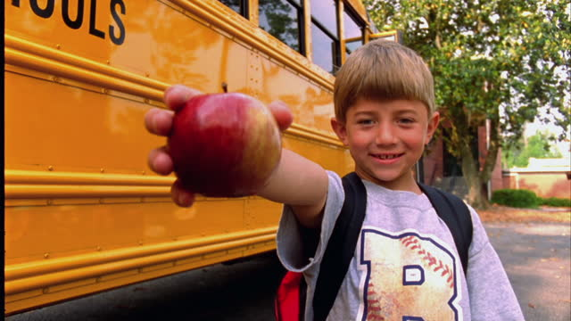 a young boy holds an apple and smiles in front of his school bus. - bangs stock videos and b-roll footage