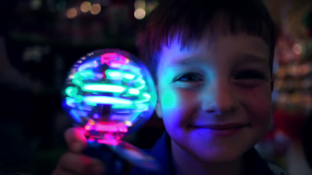 vídeos y material grabado en eventos de stock de young boy holds up spinning light to camera smiling in novelty shop looking surprised - curiosidad