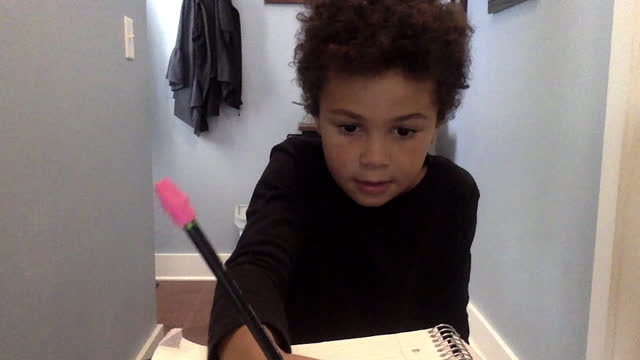 young boy in a remote learning class takes notes during video call - pencil stock videos & royalty-free footage