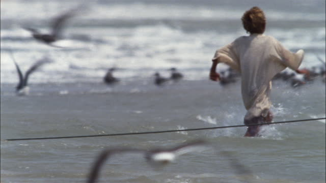 a young boy in an oversize t-shirt runs into the ocean a retrieves a plastic jug on a string. - yemen bildbanksvideor och videomaterial från bakom kulisserna