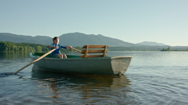 young boy in blue shirt and jeans shorts is sculling a old skiff boat on a lake while late sunlight on a beautiful summer day while digital detoxing on his summer vacations - sculling video stock e b–roll