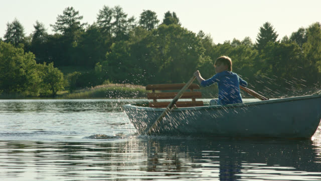 young boy in blue shirt is sculling a old skiff boat on a lake while sunset on a beautiful summer day while digital detox in his summer vacations - sculling stock videos & royalty-free footage