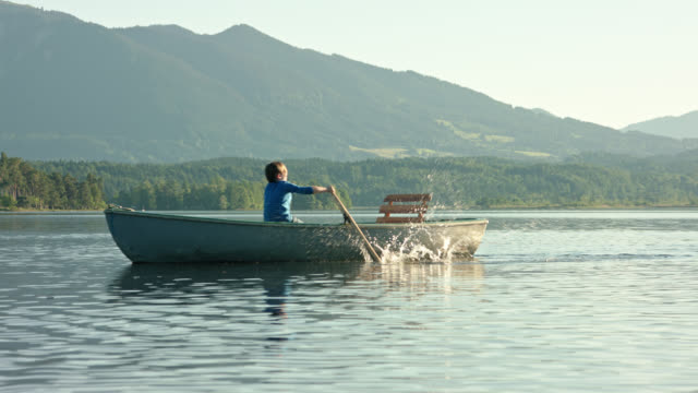 vídeos de stock e filmes b-roll de young boy in blue shirt is sculling a old skiff boat on a lake while late sunlight on a beautiful summer day while digital detox in his summer vacations - remo