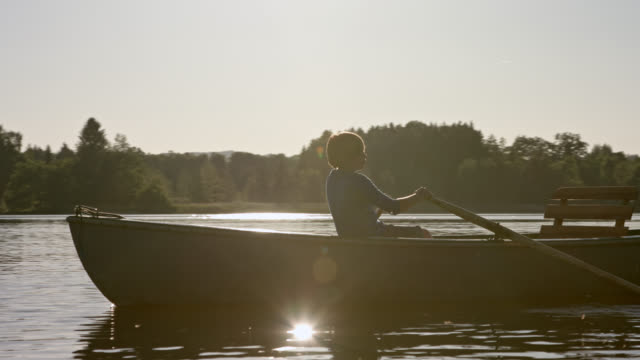 young boy in blue shirt is sculling a old skiff boat on a lake while sunset on a beautiful summer day while digital detox in his summer vacations - sculling video stock e b–roll