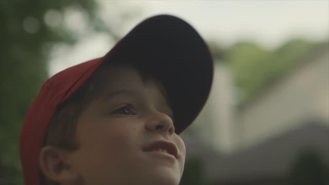 A young boy in cap throwing a baseball