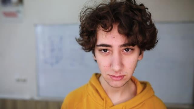 vidéos et rushes de jeune garçon dans la salle de classe regardant l'appareil-photo - sérieux