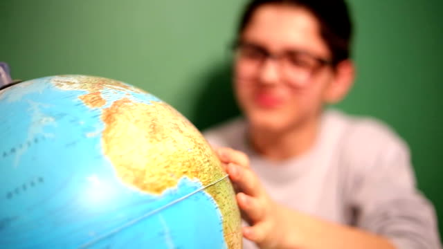 vídeos y material grabado en eventos de stock de young boy looking at the globe en montaje tipo aula - globo terráqueo para escritorio