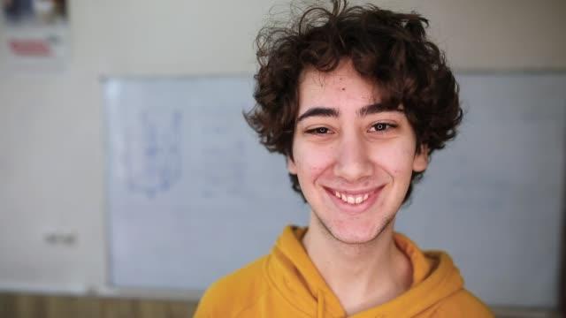 vídeos de stock, filmes e b-roll de menino novo na sala de aula que sorri na câmera - meninos adolescentes