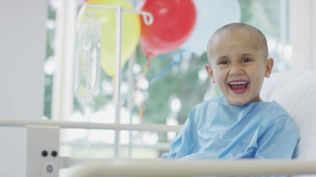 vídeos de stock e filmes b-roll de young boy in hospital laughing - cancro