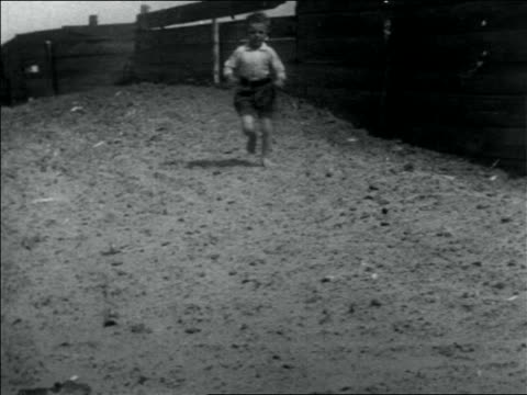 b/w 1936 young boy in shorts running toward camera / usa - running shorts stock videos and b-roll footage