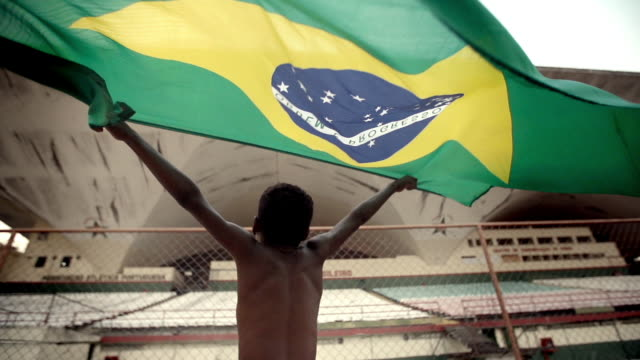 stockvideo's en b-roll-footage met young boy in soccer stadium waves brazilian flag over his head triumphantly in slow motion - brazilië