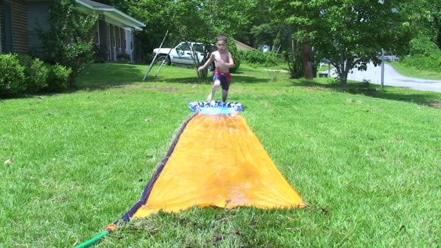 young boy in summer - water slide stock videos & royalty-free footage