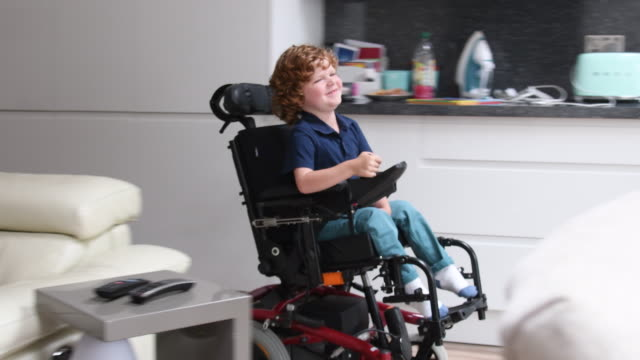 young boy in wheelchair approaching camera talking and smiling - achievement stock videos and b-roll footage