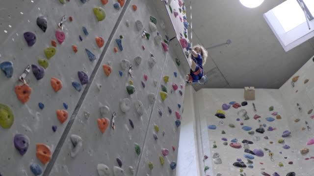 stockvideo's en b-roll-footage met jonge jongen is klimmen een indoor klimwand - alleen jongens