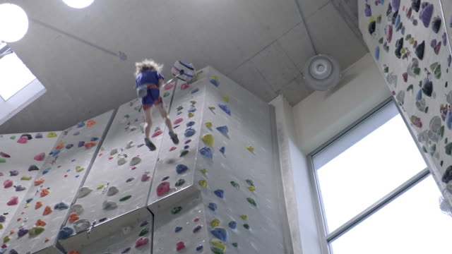 young boy is climbing an indoor climbing wall - climbing equipment stock videos & royalty-free footage