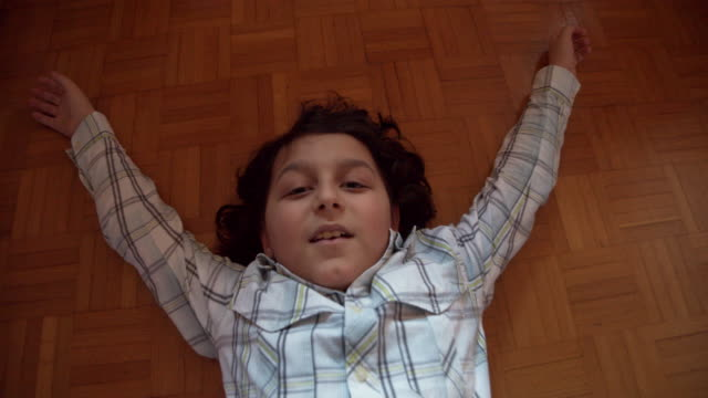 young boy is lying down on the floor, looking at camera - slow motion video - wooden floor stock videos & royalty-free footage