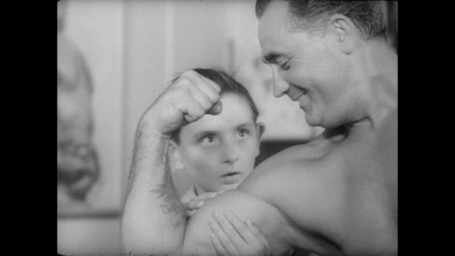Young boy is very impressed by Charles Atlas' bicep curl touches his arm
