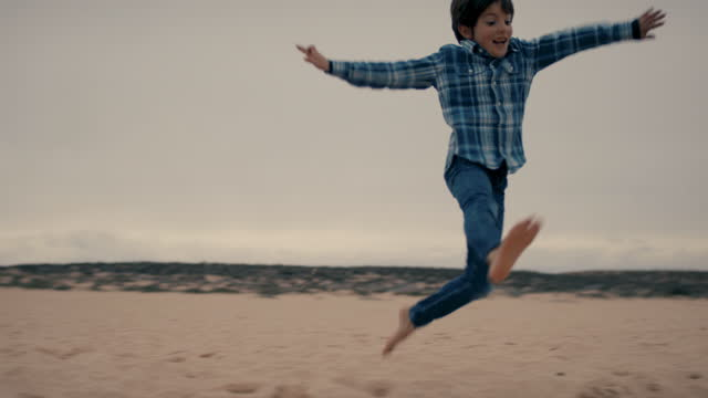 young boy jumping at beach - innocence stock videos & royalty-free footage
