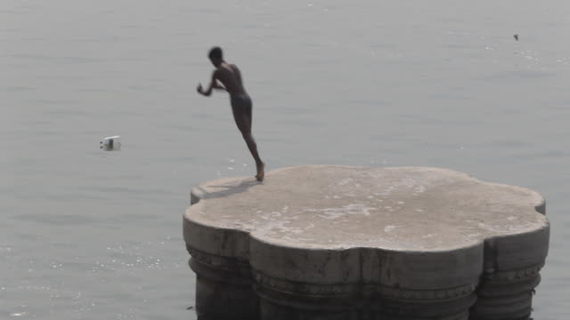 vídeos de stock, filmes e b-roll de ws young boy jumping off platform into river ganges / varanasi, india - só um menino adolescente