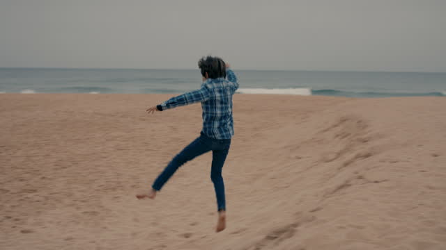stockvideo's en b-roll-footage met young boy jumping on beach with grandfather watching - innocence