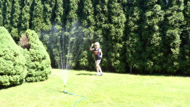 young boy jumping through water from garden sprinkler. - elementary age stock videos & royalty-free footage