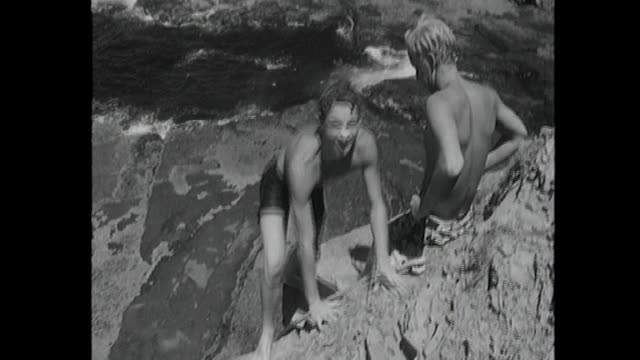 young boy jumps from headland rock cliffs into surf swims to and scrambles up onto rocks / several young men with no shirts and young woman with...