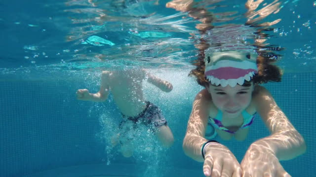vídeos de stock, filmes e b-roll de young boy jumps into pool and swims alongside a young girl, both wearing shark caps. - tubarão
