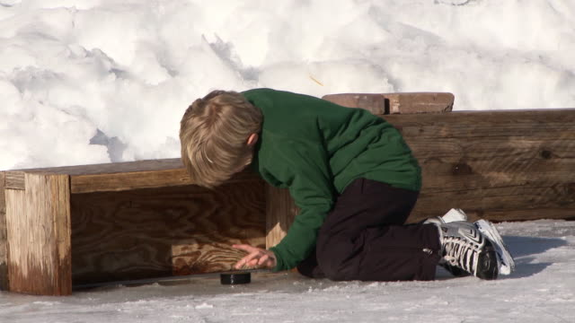 young boy kicks hockey pucks on backyard ice rink / bellevue, idaho, united states - ice rink stock videos & royalty-free footage