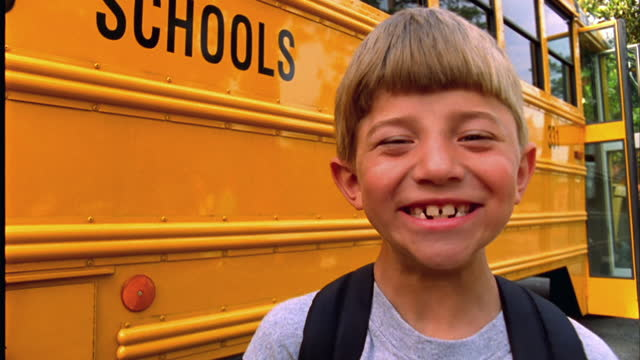 A young boy laughs in front of his school bus.