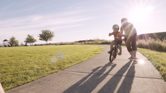 young boy learning to ride a bike - parco giochi video stock e b–roll