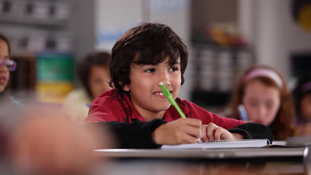 a young boy listens and takes notes from his desk during class. - pen stock videos & royalty-free footage
