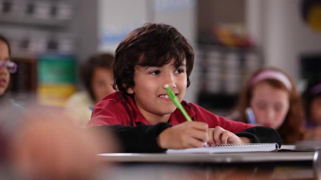 vidéos et rushes de a young boy listens and takes notes from his desk during class. - se mordre les lèvres