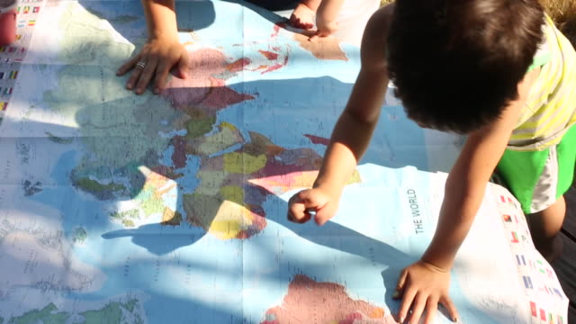 A young boy looking at a map outdoors on a sunny day.