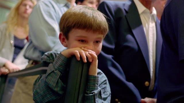 vídeos y material grabado en eventos de stock de shaky ms young boy looking bored + waiting in line at airport with other travelers in background / phoenix, az - hacer cola