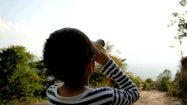 森の中で双眼鏡で風景を見ている若い男の子 - 双眼鏡点の映像素材/bロール
