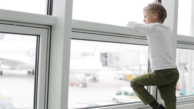 young boy looking out of a window at the airport - one boy only stock videos & royalty-free footage