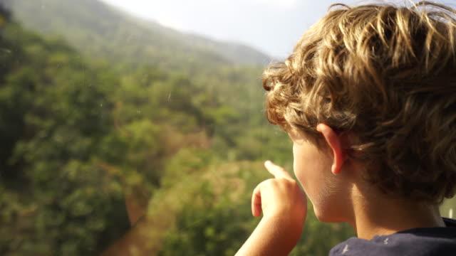 kleiner junge blick aus fenster mit seilbahn - mit dem finger zeigen stock-videos und b-roll-filmmaterial