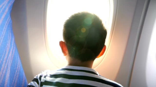 young boy looking through airplane window - air vehicle stock videos & royalty-free footage
