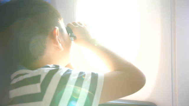 young boy looking through airplane window - passenger stock videos & royalty-free footage